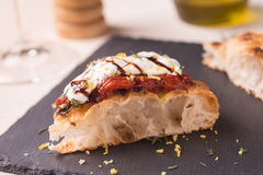 Pizza gourmet slice. Slice of pizza gourmet with backed tomato, italian burrata, balsamic winegar and grated lemon Royalty Free Stock Photo