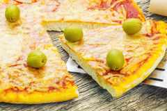 Pizza with ham and green olives on table Stock Photography