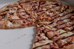 Pizza with ham and ketchup without two pieces is in the box. Advertise traditional Italian dishes. Pizza day royalty free stock images