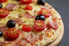 Pizza with ham, mozzarella cheese, cherry tomatoes, red pepper, black olives and oregano. Home made food. Concept for a tasty and stock photos