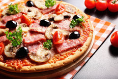 Pizza with Ham, Mushrooms, olives and parsley. Hot, delicious, juicy, fresh-cooked pizza Royalty Free Stock Image