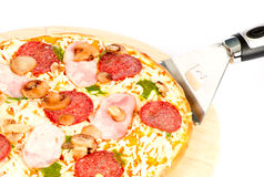 Pizza with ham, mushrooms, salami and pesto sauce Royalty Free Stock Photo