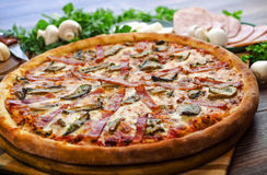 Pizza ham and mushrooms. Pizza with ham and mushrooms on a wooden table Royalty Free Stock Photo