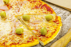Pizza with ham and olives on wooden table Stock Images
