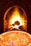 Pizza with ham and open fire in oven Stock Photography