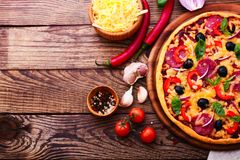 Pizza with ham, pepper and olives. Delicious fresh Royalty Free Stock Images
