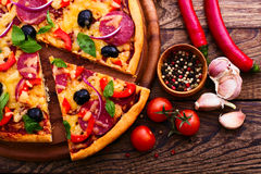 Pizza with ham, pepper and olives. Delicious fresh pizza served on wooden table. Stock Images