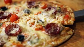 Pizza with ham, pepper, tomato and olives stock video footage