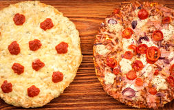 Pizza with ham and pizza 4 cheeses on the wooden background. Stock Photos