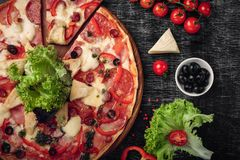 Pizza with ham, salami, cheese, mushrooms, cherry tomatoes, bell peppers and salad on a black chalk board royalty free stock photography
