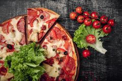 Pizza with ham, salami, cheese, mushrooms, cherry tomatoes, bell peppers and salad on a black chalk board. royalty free stock photo