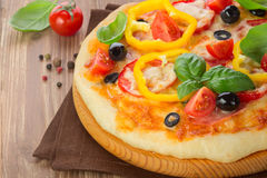 Pizza with ham, tomato and olives and vegetables Royalty Free Stock Images
