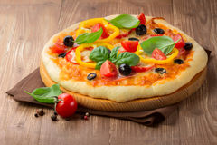 Pizza with ham, tomato and olives and vegetables Royalty Free Stock Image