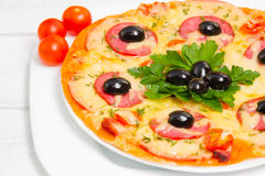 Pizza with ham, tomatoes and olives. Selective. Pizza with ham, tomatoes and olives. On the white wooden boards. Selective focus Stock Images