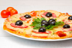 Pizza with ham, tomatoes and olives. Selective. Pizza with ham, tomatoes and olives. On the white wooden boards. Selective focus Stock Image