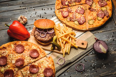 Pizza and hamburger on wooden background. With French fries red onion garlic and sweet pepper and pickles Royalty Free Stock Image