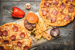 Pizza and hamburger on wooden background. With French fries red onion garlic and sweet pepper and pickles Royalty Free Stock Photo