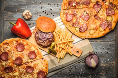 Pizza and hamburger on wooden background. With French fries red onion garlic and sweet pepper and pickles Stock Images