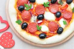 Pizza handmade with Salami, Mozzarella, Olives, Onion and Tomato Sauce Stock Photo