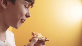 Pizza. happy teen boy eating a slice of pizza concept lifestyle . teenage boy hungry eats a slice of pizza. slow motion stock video footage