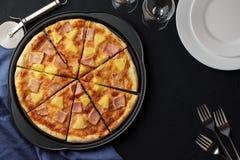 Pizza hawaiana con la piña dulce y el jamón salado en fondo de piedra oscuro con las placas, las bifurcaciones y los vidrios Foto de archivo