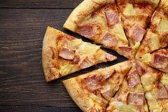 Pizza hawaiana cortada con el jamón y la piña en la tabla de madera oscura Fotografía de archivo