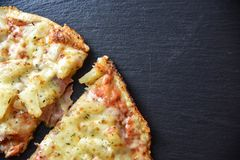 Pizza hawaii with cheese on a black stone background. Tasty Stock Image