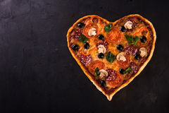 Pizza heart love Valentine`s Day romantic Italian restaurant dinner food. Prosciutto, olives, tomatoes, parsley, basil Royalty Free Stock Image