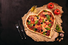 Pizza heart love Valentine`s Day romantic Italian restaurant dinner food. Prosciutto, olives, tomatoes, parsley, basil Royalty Free Stock Images