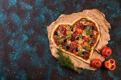 Pizza heart love Valentine`s Day romantic Italian restaurant dinner food. Prosciutto, olives, tomatoes, parsley, basil Stock Photos