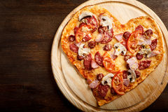 Pizza heart shape on dark wooden background top view Royalty Free Stock Photo