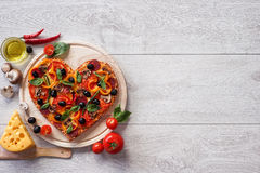 Pizza heart shape with ingredients on white wooden background. Stock Photography