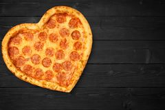 Pizza heart for Valentine`s Day romantic concept copy space on rustic dark black background. Top View. Flat lay.  stock images