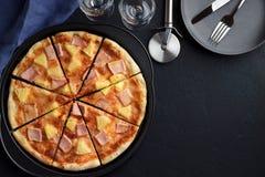Pizza hecha en casa con la piña y el jamón en la tabla de piedra azul marino con vajilla Imagenes de archivo