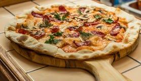 Pizza hecha en casa con los salchichones foto de archivo
