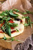 Pizza hecha en casa con los tomates y los brotes que rematan en la tabla rústica Foto de archivo libre de regalías