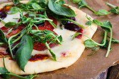 Pizza hecha en casa con los tomates y los brotes que rematan en la tabla rústica Imágenes de archivo libres de regalías