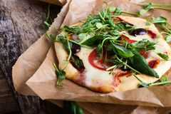 Pizza hecha en casa con los tomates y los brotes que rematan en la tabla rústica Fotografía de archivo libre de regalías