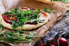 Pizza hecha en casa con los tomates y los brotes que rematan en la tabla rústica Foto de archivo