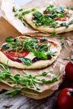 Pizza hecha en casa con los tomates y los brotes que rematan en la tabla rústica Fotografía de archivo