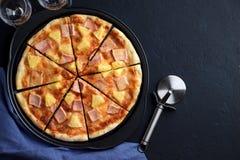 Pizza hecha en casa Hawaii con la piña y el jamón en fondo de piedra oscuro Fotografía de archivo