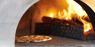 Pizza in hete brandhoutoven voor kok stock afbeeldingen