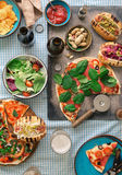 Pizza, hot dog grilled, salad, lager and snacks to beer. Italian pizza, hot dog grilled, salad, lager and snacks to beer, top view. Dinner table with various royalty free stock photography