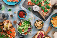 Pizza, hot dogs, wine, beer and a snack for beer. Outdoors food concept. Pizza, hot dogs, wine, beer and a snack for beer on the table, top view royalty free stock photos