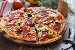 Pizza with hum, cheese, tomato and pepper royalty free stock photography
