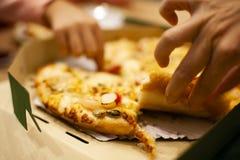 Pizza i ask på tabellen på pizzalagret var hackan som ska ätas vid två händer av dotter och modern för matställe arkivfoto