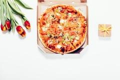 Pizza i en ask, röda tulpan och en liten ask med en gåva på en whit Arkivfoton