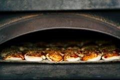 Pizza i en ugn royaltyfria foton