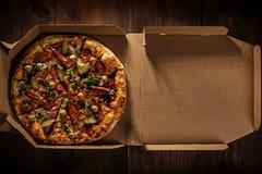 Pizza i i leveransask på trät royaltyfri bild