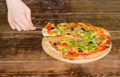 Pizza i pizza plasterek na pizzy szpachelce w ręce Fotografia Stock